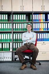 Man sitting chair filing cabinet office relaxed