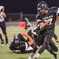 Crownpoint Eagle Isaiah Pool (27) attempts to evade the Newcomb Skyhawks defense Friday at Crownpoint High School.