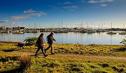 A man and a woman walk a dog at the marina at Pwllheli, North Wales, UK<br /> <br /> (c) Andrew Wilson   Edinburgh Elite media