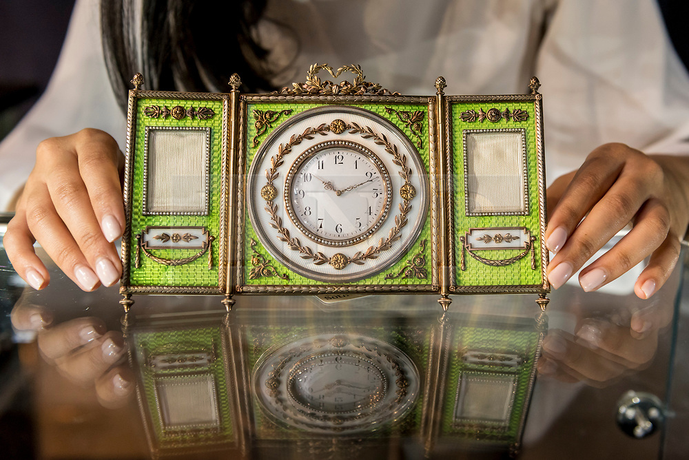 """© Licensed to London News Pictures. 31/05/2019. LONDON, UK. A staff member presents """"A rare Fabergé silver-gilt enamel and seed pearl triptych clock and frame"""" by workmaster Johan Victor Aarne, 1880-1904 (Est. GBP 150,000-200,000) at a preview of works from the upcoming sale of Russian Pictures, Works of Art, Fabergé & Icons Sales at Sotheby's, New Bond Street, on 4 June 2019.  Photo credit: Stephen Chung/LNP"""
