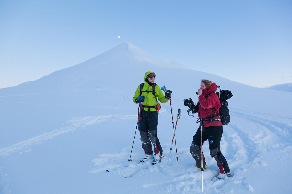 Nate Stevens (left) and Anouk Vlug share chocolate at dusk below Hallwylfjellet, Svalbard.