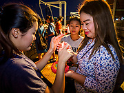 "03 NOVEMBER 2017 - BANGKOK, THAILAND: Girls light incense in their krathong during Loi Krathong at Wat Prayurawongsawat on the Thonburi side of the Chao Phraya River. Loi Krathong is translated as ""to float (Loi) a basket (Krathong)"", and comes from the tradition of making krathong or buoyant, decorated baskets, which are then floated on a river to make merit. On the night of the full moon of the 12th lunar month (usually November), Thais launch their krathong on a river, canal or a pond, making a wish as they do so. Loi Krathong is also celebrated in other Theravada Buddhist countries like Myanmar, where it is called the Tazaungdaing Festival, and Cambodia, where it is called Bon Om Tuk.     PHOTO BY JACK KURTZ"