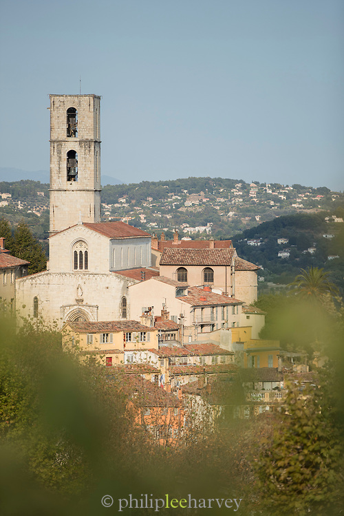 Old town buildings with bell tower of Grasse Church view from behind trees, Grasse, France