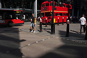 A red Routemaster London bus on the number 15 route drives along Cannon Street, on 24th August 2016, in the City of London, UK. A pedestrian steps out to cross a side street past this busy road running across the capitals financial district, founded by the Romans in the first Century.