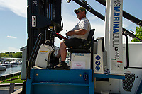 Rick Morin operates the fork lift putting in a 25' Barletta Pontoon boat into Lake Winnipesaukee at Mountain View Yacht Club on Wednesday.  (Karen Bobotas/for the Laconia Daily Sun)