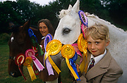 "Two young girls stand with their beloved ponies at a gymkhana in Cheltenham, Gloucestershire. Adorned with winners' rosettes, the horses look their finest for the judges. The girls are smart too, wearing the expected jackets and ties, jodhpurs and during competition, helmets too. The word gymkhana is an Indian Raj term which originally referred to a place where sporting events took place and referred to any of various meets at which contests were held to test the skill of the competitors. In the UK and east coast of the US, the term gymkhana now almost always refers to an equestrian event for riders on horses, often with the emphasis on children's participation (such as those organised here by the Pony Club). Gymkhana classes include timed speed events such as barrel racing, keyhole, keg race (also known as ""down and back""), flag race, and pole bending."