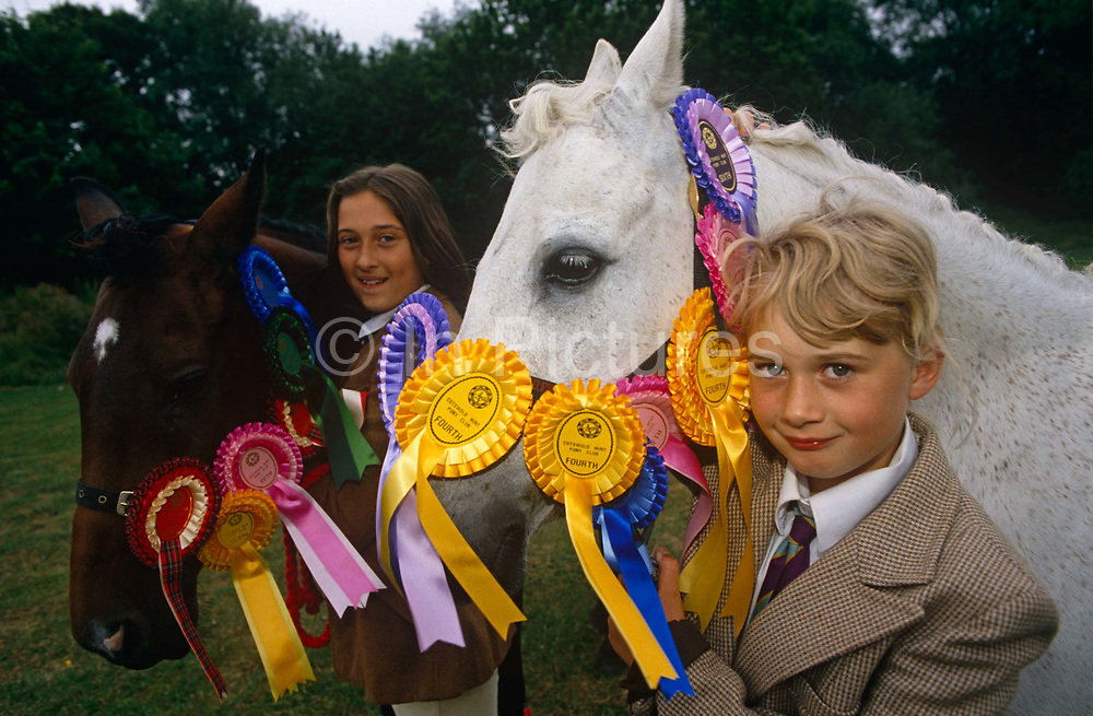 """Two young girls stand with their beloved ponies at a gymkhana in Cheltenham, Gloucestershire. Adorned with winners' rosettes, the horses look their finest for the judges. The girls are smart too, wearing the expected jackets and ties, jodhpurs and during competition, helmets too. The word gymkhana is an Indian Raj term which originally referred to a place where sporting events took place and referred to any of various meets at which contests were held to test the skill of the competitors. In the UK and east coast of the US, the term gymkhana now almost always refers to an equestrian event for riders on horses, often with the emphasis on children's participation (such as those organised here by the Pony Club). Gymkhana classes include timed speed events such as barrel racing, keyhole, keg race (also known as """"down and back""""), flag race, and pole bending."""