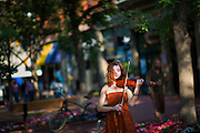 A young woman performs classical music on the violin on the pedestrian Pearl Street Mall in Boulder, Colorado.