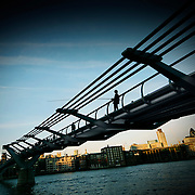 A silhouetted man fishing off the Millennium Bridge over the River Thames in central London.