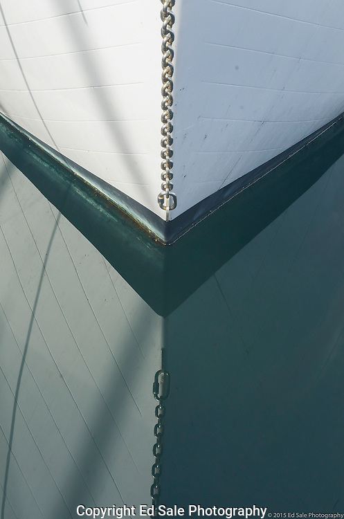 The white bow of a wooden boat with a chain is reflected in the water while at moorage in the marina at Winslow, Washington.