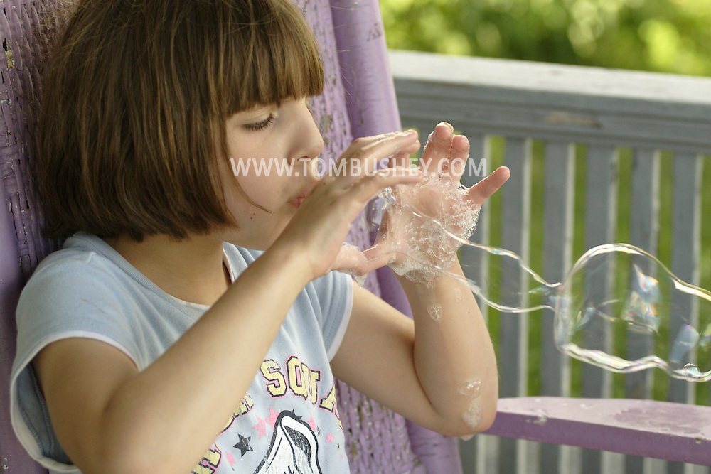 Middletown, NY  - An 8-year-old girl blows bubbles while sitting on her front porch on June 27, 2007. MR