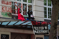 Pro-Palestinian activists from Palestine Action occupy an area above the entrance to the headquarters of Elbit Systems UK, daubing it with painted messages, on 6th August 2021 in London, United Kingdom. The activists were protesting against the presence in the UK of Elbit Systems, an Israel-based company developing technologies for military applications including drones, precision guidance, surveillance and intruder-detection systems used against the Palestinians, and their action formed part of a concerted campaign by Palestine Action against the Israeli arms company.