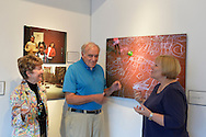 Huntington, New York, USA. August 1, 2015. L-R, HOLLY GORDON, GEORGE CARRANO and LOIS YOUMANS are talking at the Reception for Project Lives exhibition at fotofoto gallery. Over 200 residents throughout 15 New York Public Housing projects were given single use film cameras to photograph what's important to them in their world. The photography project was originated by Carrano and the book Project Lives was edited by Carrano, C. Davis and J. Fisher, with all royalties from its sale to be donated to resident programs at NYC Housing Authority. Gordon is a member and Youmans is the President of the gallery, on the Gold Coast of Long Island. The photos are: three young girl friends by Angelly Sureo, snow scene by Susana Ortiz, and girl with chalk drawings on porch floor by Sheik Bacchus.