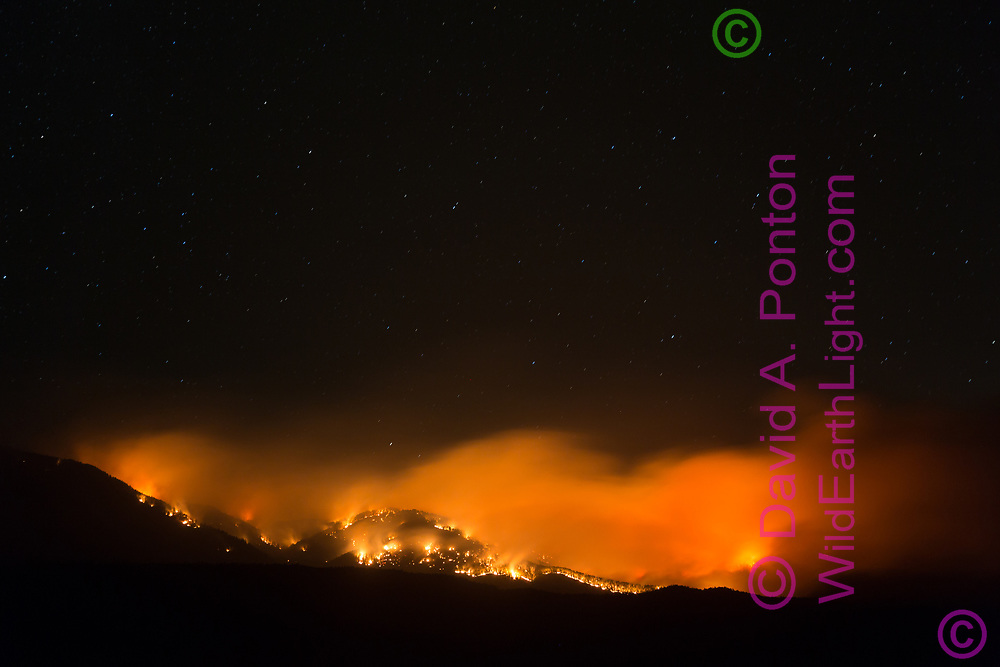 Thompson Fire backburn along the ridge leading SE from Redondo Peak, South Mountain prominent, night of June 8, 2013, viewed from the southwest. Valles Caldera National Preserve, New Mexico, © 2013 David A. Ponton