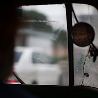 A mototaxi driver in the mirror of his vehicle