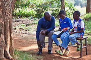A couple of young boys study with their teacher at the AFCIC centre in Thika, Kenya. AFCIC - Action for children in conflict, help children who have been affected by various forms conflict or crisis.