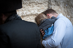 19 April 2019, Jerusalem: A man and his daughter pray by the Western Wall. On the first day of Pesach (Passover) Jews gather to pray by the Western Wall in Jerusalem, considered as the most sacred and holy place for the Jews.