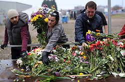 Volunteers help to relocate flowers, left for the victims of the Helicopter crash, to a new memorial site at the King Power Stadium, Leicester.