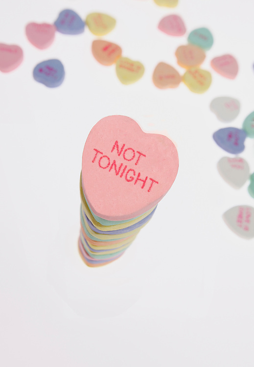 """Assorted candy on table and a column of the candy with """"not tonight"""" as the inscription on the top piece"""