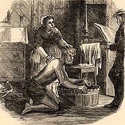 A coal miner cleaning up after  work with the help of his wife. Before the days of piped water and pit-head baths, after a day hewing coal underground the miner had only a tub on the living room floor filled with water from an outside pump to wash away the coal dust from his skin.  Northumberland and Durham Coalfield, England.   Engraving from 'The Graphic' (London, 18 February 1871).