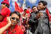 08 MAY 2013 - BANGKOK, THAILAND:   A Red Shirt protester makes a mobile phone call during a protest motorcade to the Thai parliament building. A splinter group of the Red Shirts, Thai supporters of exiled Prime Minister Thaksin Shinawatra, have besieged the Thai Constitutional Court for the last three weeks calling for the resignation of the justices, who have indicated they might oppose a proposed constitutional reform which would grant amnesty to people convicted of political crimes since 2007. This would probably include Thaksin. The justices have refused to step down. Wednesday the protesters moved their protest to the Thai Parliament, which is largely powerless to intervene. PHOTO BY JACK KURTZ