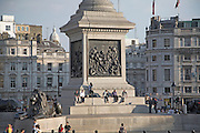 People sitting at the base of Nelson's column, Trafalgar Square, London, England