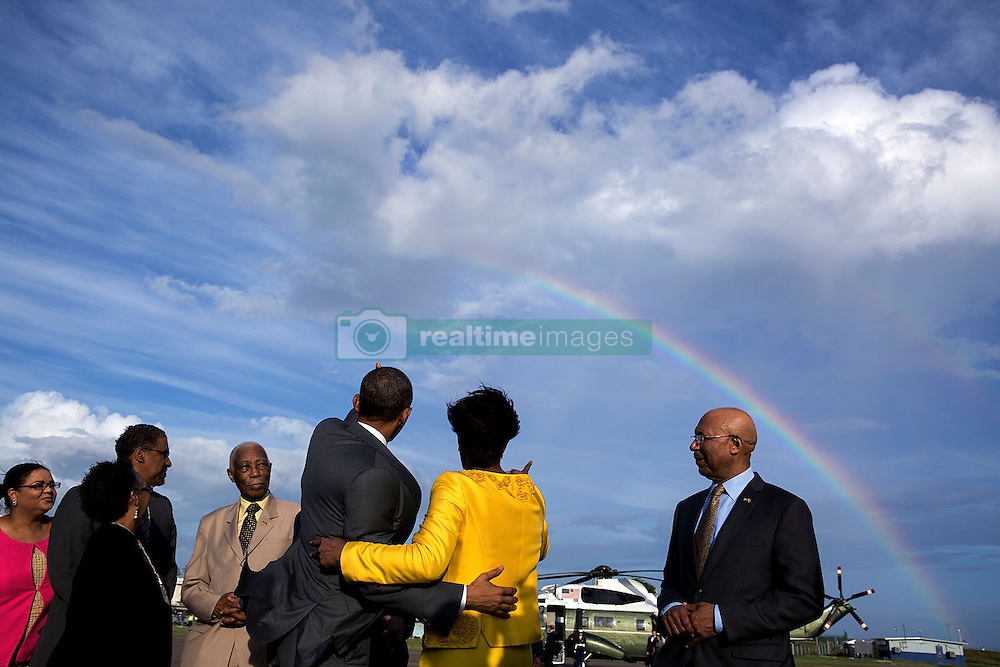 President Barack Obama and Jamaican Prime Minister Portia Simpson-Miller gesture toward a rainbow at Norman Manley International Airport prior to the President's departure from Kingston, Jamaica, April 9, 2015. (Official White House Photo by Pete Souza)<br /> <br /> This official White House photograph is being made available only for publication by news organizations and/or for personal use printing by the subject(s) of the photograph. The photograph may not be manipulated in any way and may not be used in commercial or political materials, advertisements, emails, products, promotions that in any way suggests approval or endorsement of the President, the First Family, or the White House.