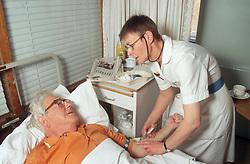 Female nurse attending to elderly patient in hospital bed,