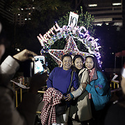 """Hong Kong has a huge population of Filipinos, mostly woman who work as domestic workers in the business community. Here Filipino women celebrate Christmas together out door in downtown Hong Kong, most Filipinos are Catholics.   <br /> <br /> Hong Kong (香港; """"Fragrant Harbour""""), officially known as Hong Kong Special Administrative Region of the People's Republic of China since the hand-over from the United Kingdom in 1997 under the principle of """"one country, two systsems"""".  7 million people live on 1,104km square, making it the most vertivcal city in the world. Hong Kong is one of the world's leading financial centres along side London and New York, it has one of the highest income per capita in the world as well the moste severe income inequality amongst advanced economies. The Hong Kong civil society is highly regulated but has at the same time one of the most lassiez-faire economies with low taxation and free trade. Civil unrest and political dissent is unusual but in 2014 the Umbrella Movenment took to the streets of Hong Kong demanding democracy and universal suffrage. 93 % are ethnic Chinese, mostly Cantonese speaking."""