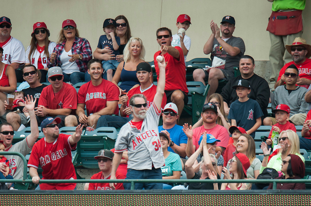 An Angel fan celebrates catching a foul ball during the Angels' 13-inning 8-6 loss to the Houston Astros Sunday at Angel Stadium. <br /> <br />  //ADDITIONAL INFO:   <br /> <br /> angels.0530.kjs  ---  Photo by KEVIN SULLIVAN / Orange County Register  -- 5/29/16<br /> <br /> The Los Angeles Angels take on the Houston Astros Sunday at Angel Stadium.