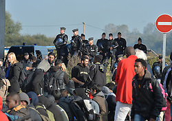 Police create a cordon as several large fires broke out in the near deserted migrant camp in Calais, northern France on the third day of the operation to clear it.