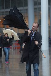 © Licensed to London News Pictures. 21/10/2014. London, UK. A commuters struggles to control his umbrella as he leaves London Bridge station during heavy rain and wind in the City of London this morning, 21st October 2014 after the end of Hurricane Gonzalo reached the UK overnight. Photo credit : Vickie Flores/LNP