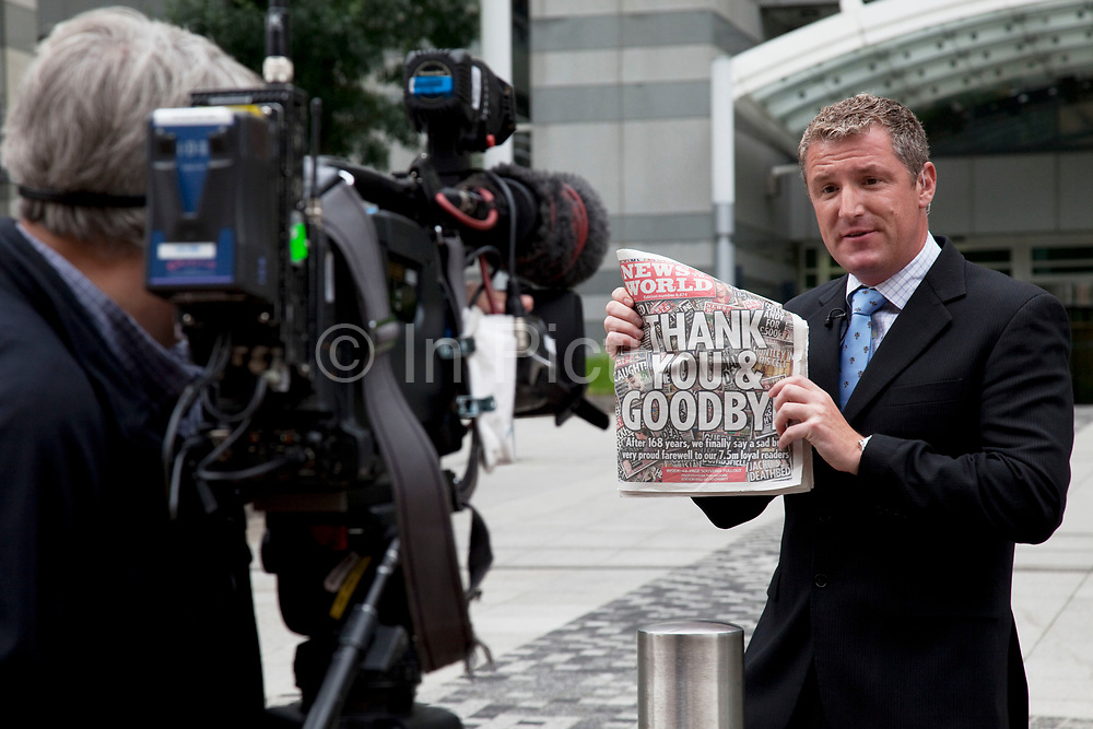 """The last ever copy of tabliod newspaper News of The World is shown to the camera by a news anchor outside their offices in Wapping. Sunday 10th July 2011 saw the end for this most famous of newspapers. Embroiled in the phone hacking scandal, this News International paper had approximately 7 million readers at the time of it's demise. On the cover of this, the final edition, with examples of previous journalistic success the headline simply read """"Thank You & Goodbye""""."""
