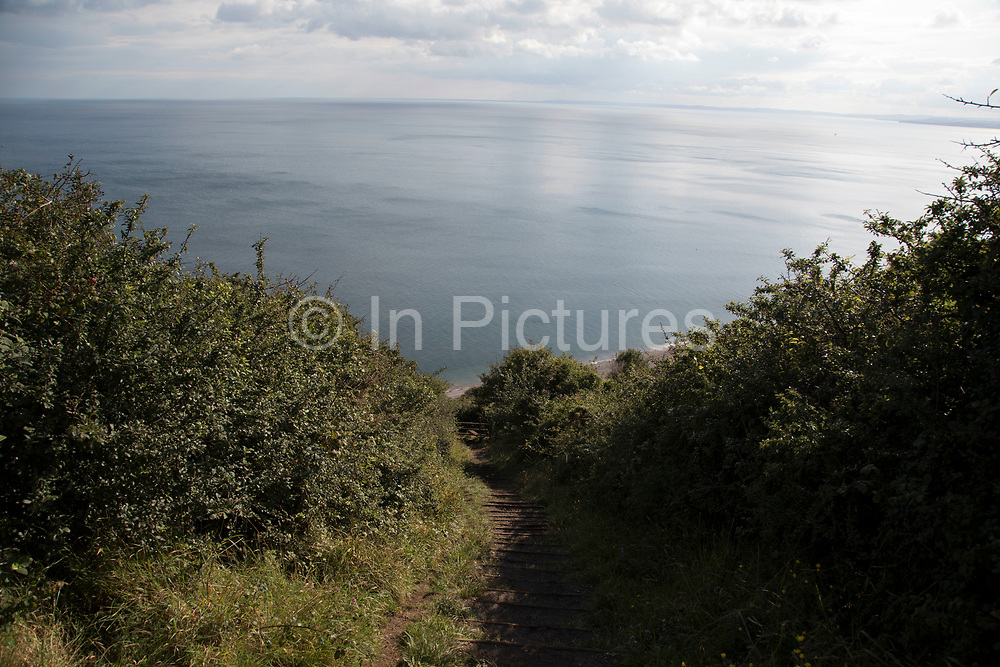 Coastal seaside view at Branscombe, Devon, England, United Kingdom. It is located within the East Devon Area of Outstanding Natural Beauty, overlooking Lyme Bay. The village straggles along narrow roads down steep-sided valleys, terminating at a shingle beach, Branscombe Mouth, which forms part of the East Devon and Dorset Jurassic Coast. To either side of the beach, the coast rises steeply to cliffs, which are in the ownership of the National Trust. It is a popular point for starting walks on the South West Coast Path.