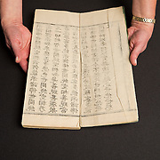 Luise Poulton, Rare Books Manager Special Collections  holds a copy  a 15th-century tome of sacred Buddhist writings, titled Da ban ruo bo luo mi duo jing, from China.in the rare book collection at the J. Willard Marriott Library on the campus of the University of Utah in Salt Lake City, Utah Wednesday Oct. 10, 2012. (Photo by August Miller).