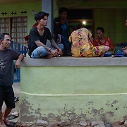 People gather outside their small homes on the streets of Komodo in the early evening. Komodo Island, Indonesia.