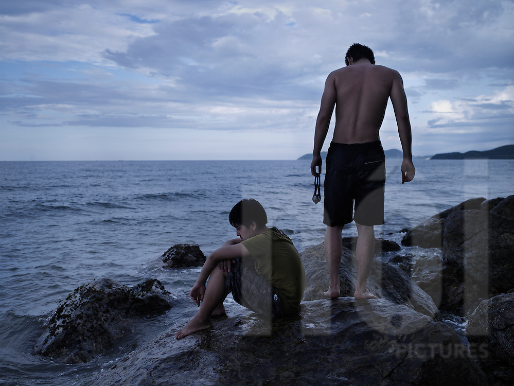 Boys rest on rocks by the sea shore and look down into the ocean, Dong Hoi, Quang Binh Province, Vietnam, Southeast Asia