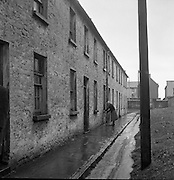 Limerick Widows Alms House.  Widow Mrs. Mary Kelly (72) gets drinking water from the communal tap..28.03.1962