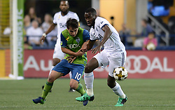September 27, 2017 - Seattle, WASHINGTON, U.S - Soccer 2017: Sounders midfielder NICHOLAS LODEIRO (10) and Whitecaps midfielder TONY TCHANI (16) battle for the ball as the Vancouver Whitecaps visit the Seattle Sounders for an MLS match at Century Link Field in Seattle, WA. (Credit Image: © Jeff Halstead via ZUMA Wire)