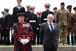 London, June 23rd 2014. M ayor of London Boris Johnson joins a Yeoman Warder and members and veterans of the armed forces at City Hall for a flag raising ceremony to mark Armed Forces Day.