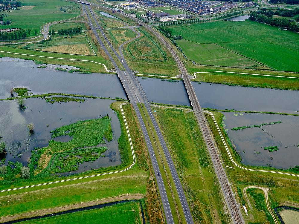 """Nederland, Overijssel, Gemeente Kampen; 21–06-2020; het Reevediep ter plaatse van Reevediepbrug(rijksweg N50) en Spoorbrug Reevediep, station Kampen-Zuid in de achtergrond.<br /> Het Reevediep is aangelegd in het kader van het project Ruimte voor de Rivier om bij hoogwater water af te voeren voordat dit het nabij gelegen Kampen bereikt, direct naar het IJsselmeer, de 'bypass Kampen'. Het Reevediepgebied is ook een natuurgebied en vormt een ecologische verbindingszone tussen rivier de IJssel en Drontermeer.<br /> Reevediep at the location of the Reevediep Bridge (national road N50) and the Reevediep Railway Bridge, Kampen-Zuid station in the background. The Reevediep has been constructed as part of the Room for the River project, and functions to discharge high waters before reaching the nearby Kampen, directly to the IJsselmeer, the """"bypass Kampen"""". The Reevediep area is also a nature reserve and forms an ecological connecting zone between the river IJssel and Drontermeer.<br /> <br /> luchtfoto (toeslag op standaard tarieven);<br /> aerial photo (additional fee required)<br /> copyright © 2020 foto/photo Siebe Swart"""
