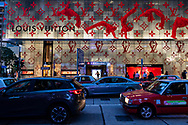 Hong Kong - August 26, 2019: Evening traffic outside a Louis Vuitton store in the Central district of Hong Kong. A subway entrance is in the center of the building.