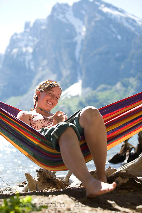 Young woman writing in journal while sitting in hammock on Jackson Lake. Grand Teton NP, WY.