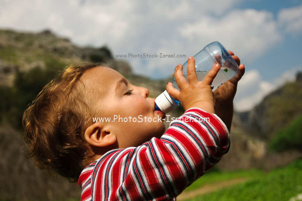 Young toddler of 18 months drinks mineral water from a bottle outdoors