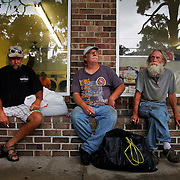 """Joe Crow, of Beaufort, N.C., Rocky Rochelle, of Beaufort, N.C., and Jim Marks, aka """"Fuzzy,"""" of Beaufort N.C., sit outside of the Port Royal Laundromat-Car-Wash watching the rain come in and waiting for their clothes to dry on June 23, 2014.  The men are shrimpers aboard the vessel Captain Jimmy and are spending the night in Port Royal after leaving Beaufort N.C."""
