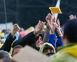 Fans catch ponchos from the stewards.  My Chemical Romance on the Main Stage..T in the Park on Sunday 10th July 2011. T in the Park 2011 music festival takes place from 7-10th July 2011 in Balado, Fife, Scotland..©Pic : Michael Schofield.