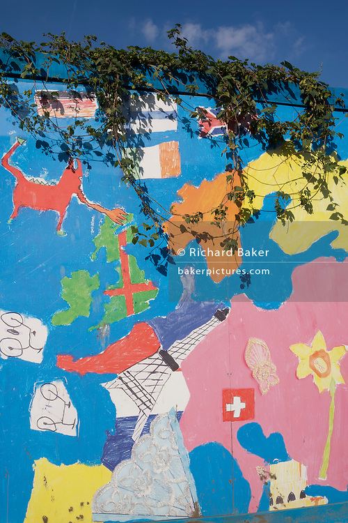 Local school childrens' artwork of Europe printed on large hoardings on perimeter wall of 2012 Olympic construction site.