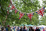 Union Jack bunting hangs over a British summer fete bringing the local community together and to celebrate their important public space, on 24th June 2017, in Ruskin Park, the south London borough of Lambeth, England. Bunting is a festive decoration made of fabric, or of plastic, paper or even cardboard in imitation of fabric. Typical forms of bunting are strings of colorful triangular flags and lengths of fabric in the colors of national flags gathered and draped into swags or pleated into fan shapes. The term is also used to refer to a collection of flags, and particularly those of a ship. The officer responsible for raising signals using flags is known as bunts, a term still used for a ship's communications officer.