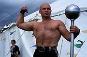 A strong man poses outside Gifford Circus, Marlborough, UK.