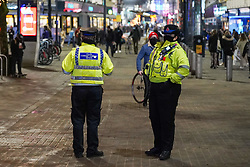 © Licensed to London News Pictures. 30/12/2020. Manchester, UK.  Police officers wearing face masks patrolling  Manchester City ahead of Tier 4 restrictions come into force. The county of Greater Manchester from Thursday 31 December will move into Tier 4 following a spike in coronavirus cases. Photo credit: Ioannis Alexopoulos/LNP
